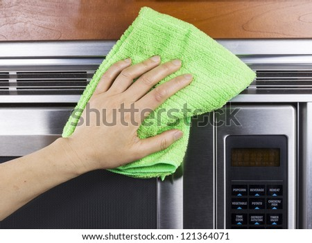 Hand with microfiber rag cleaning vents of microwave oven - stock photo