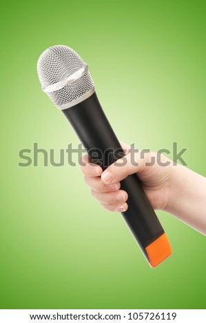 Hand with Microphone on Green - stock photo