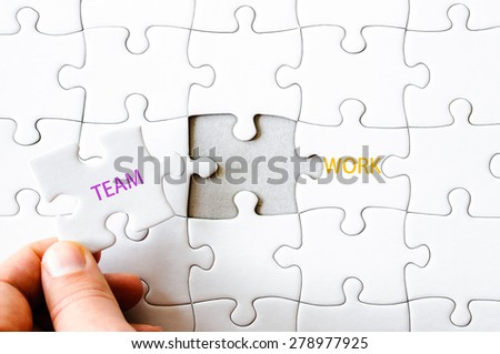 Hand with missing jigsaw puzzle piece completing the word TEAMWORK. Business concept image for completing the final puzzle piece. - stock photo