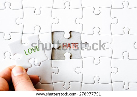 Hand with missing jigsaw puzzle piece. Word LOVE, covering  text HATE. Business concept image for completing the final puzzle piece. - stock photo
