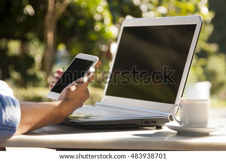 hand with mobile phone on the notebook computer