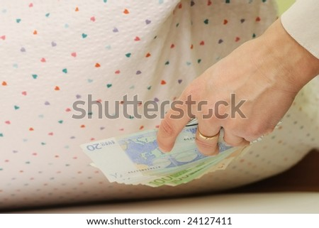 Hand with money hides them under pillow - stock photo