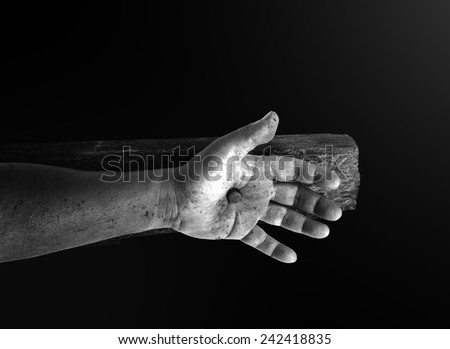 Hand with nail on the cross. - stock photo