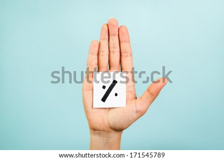 Hand with open palm showing a percentage symbol/sign on blue background. - stock photo