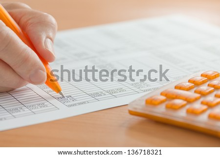 Hand with Orange Pen and Calculator Analyzing Spreadsheet Figures  - stock photo