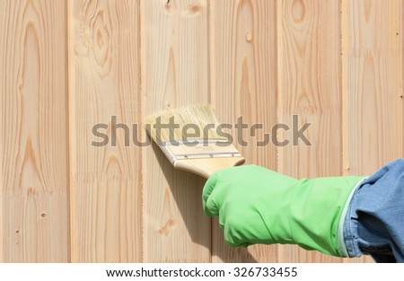 hand with paintbrush on wood  - stock photo
