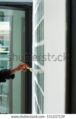 Hand with paintbrush painting a window white - stock photo