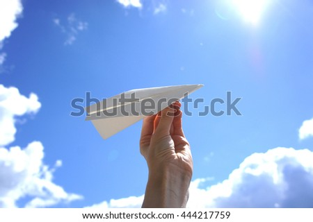 Hand with paper plane on a background of clouds