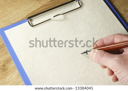 Hand with pen about to write on a piece of paper on a blue clipboard with space for text. - stock photo