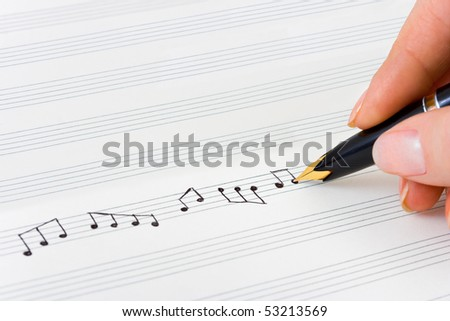 Hand with pen and music sheet - musical background - stock photo