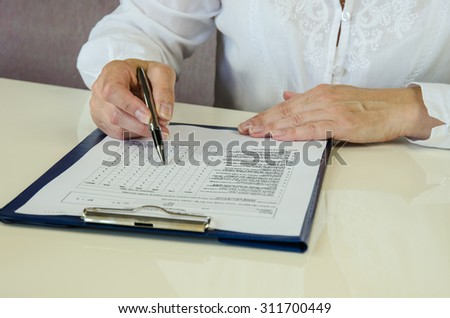 hand with pen and paperwork over desk