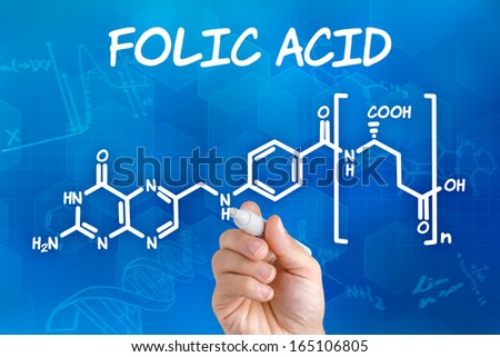 Hand with pen drawing the chemical formula of folic acid - stock photo