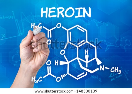 hand with pen drawing the chemical formula of heroin - stock photo