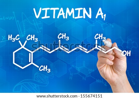 Hand with pen drawing the chemical formula of Vitamin A - stock photo