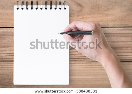 Hand with pen is going to write something on a blank notebook. Top view. - stock photo