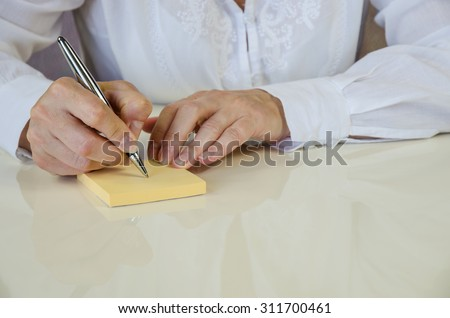 hand with pen making note in yellow sticker