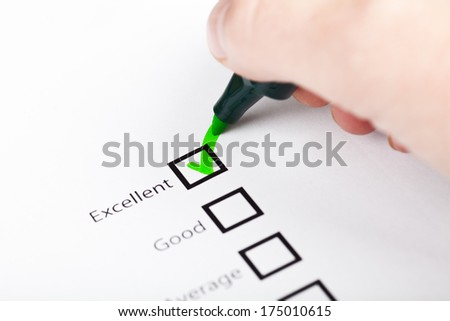 Hand with pen marking a check box  - stock photo