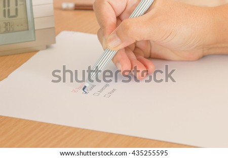 hand with pen marking check box, check list for evaluation - stock photo