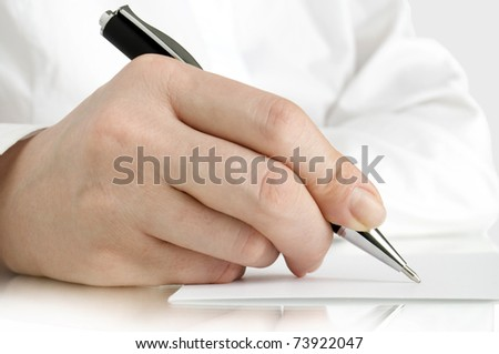 hand with pen of person in white shirt writing on the white page and reflection
