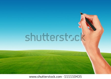 Hand with pen on blue sky and green grass - stock photo