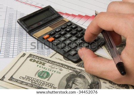 Hand with pen on finances diagrams