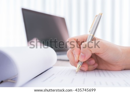 Hand with pen over application form - stock photo