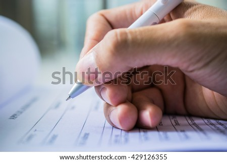 Hand with pen over application form on blure water glass background - stock photo