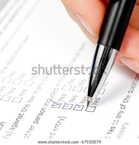 Hand with pen over blank check box Yes in application form - stock photo