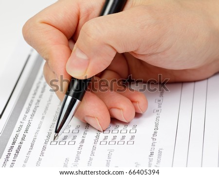 Hand with pen over blank check boxes in application form - stock photo