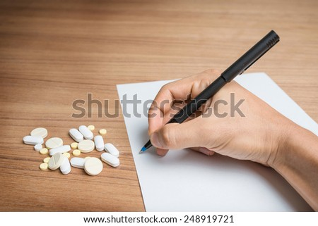 Hand with pen over blank paper form with pills. - stock photo