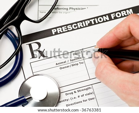 Hand with pen over blank vet prescription form with stethoscope and glasses - stock photo