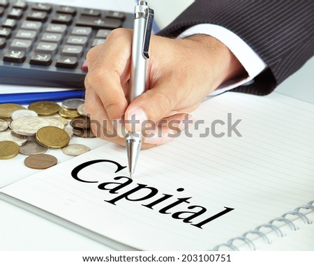 Hand with pen pointing to Capital word on the paper - business & financial concept - stock photo