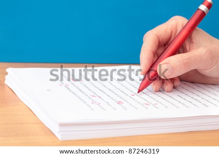 Hand with Pen Proofreading a Manuscript - stock photo