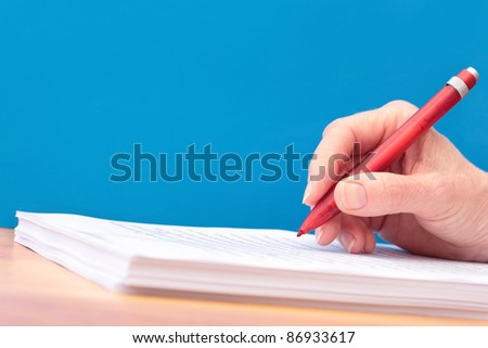 Hand with Pen Proofreading a Manuscript - undiscernable text so can be any Language