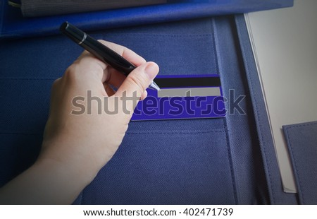 Hand with pen sign or writing down at the back of credit card
