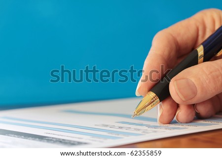 Hand with Pen Signing Form Closeup on Blue Background - stock photo