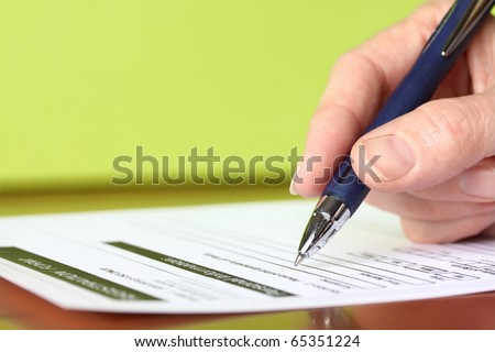 Hand with Pen Signing Form Closeup on Green Background