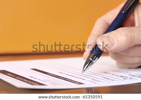 Hand with Pen Signing Form Closeup on Orange Background - stock photo