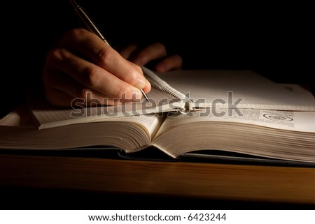 Hand with pen taking notes from an open book - stock photo