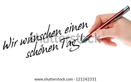 Hand with pen writes the german words Have a nice day / Have a nice day