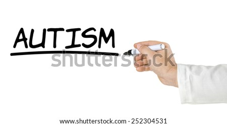 Hand with pen writing Autism - stock photo