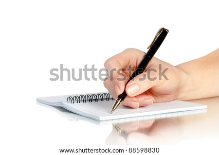 hand with pen writing on notebook and reflection - stock photo