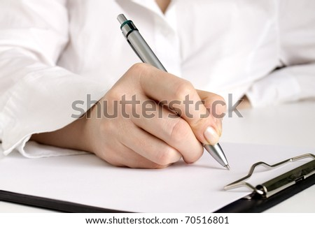 hand with pen writing on the white page in clipboard - stock photo