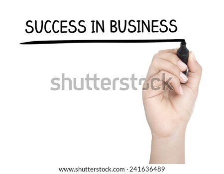 Hand with pen writing SUCCESS IN BUSINESS on whiteboard - stock photo