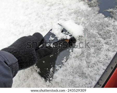 Hand with plastic cleaner cleaning snow from car window       - stock photo