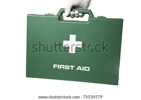 Hand with plastic gloves carrying green first aid case. - stock photo