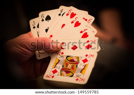 Hand with poker cards - stock photo