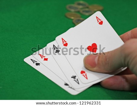 hand with poker of aces on a green table game