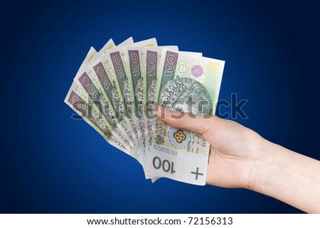 Hand with polish money on blue background - stock photo