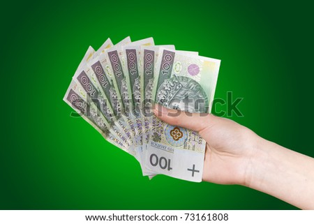 Hand with polish money on green background - stock photo